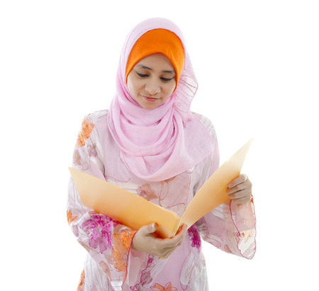 malay muslim girl reading from a folder photo