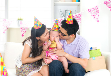 asian chinese parent kissing baby on birthday party Stock Photo