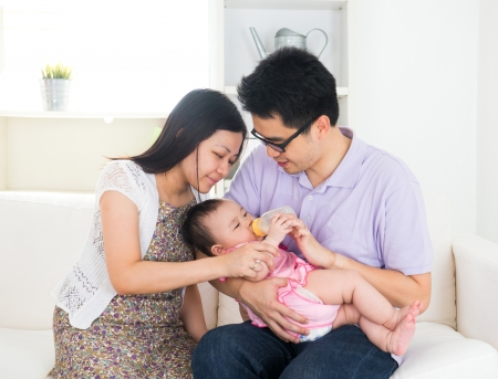 asian parents feeding baby boy at home photo