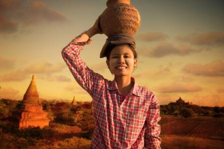 幸せなアジアの伝統的な農民収穫ミャンマー バガンで運ぶ鍋バガンに家に戻る