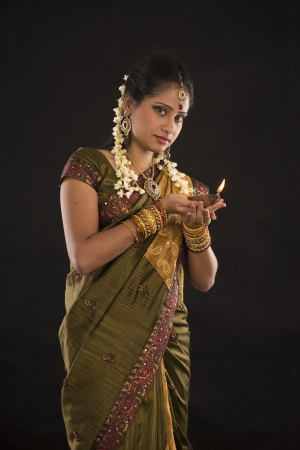 diwali or deepavali photo with female holding oil lamp during festival of light