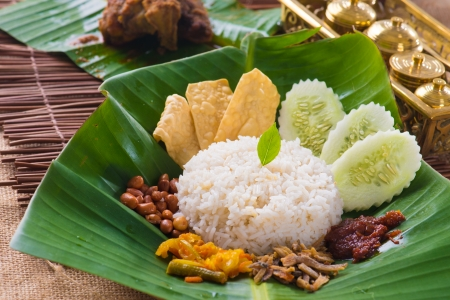 nasi lemak, a traditional malay curry paste rice dish served on a banana leaf Stock Photo - 23200797