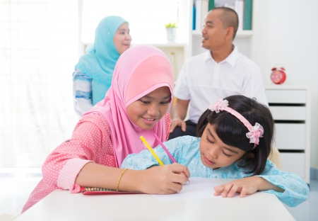 malay indonesia Muslim family colouring at home.  photo