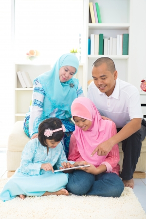malay indonesian family surfing internet at home.  photo