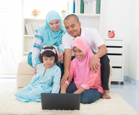 middle eastern families: malay indonesian family surfing internet at home.  Stock Photo