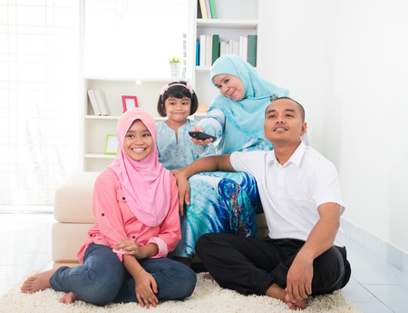 woman watching tv: malay family watching television enjoying quality time