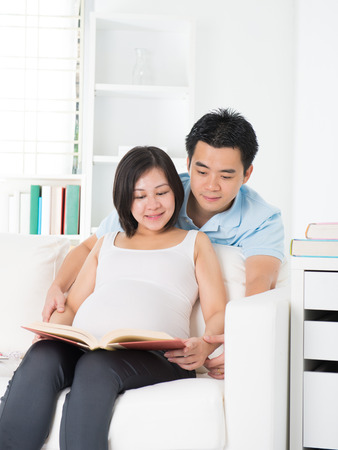 chinese pregnant father and mother reading photo