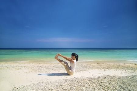 asian female performing beach yoga