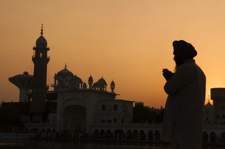 sikh: Silhouette of praying sikh man at golden temple of Amritsar, India