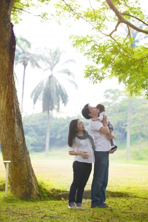 asian pregnant mother father carrying daughter outdoor   photo