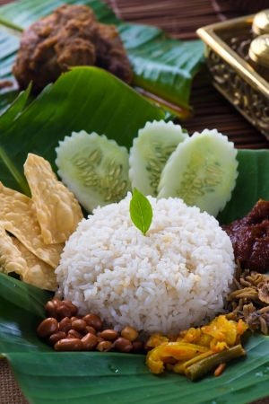 malaysian food: nasi lemak, a traditional malay curry paste rice dish served on a banana leaf