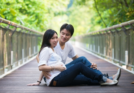 paternal: Happy young pregnant asian couple in the nature