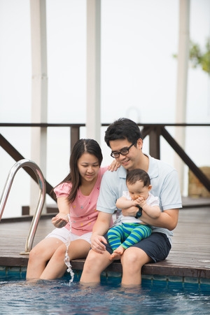 resorts: Happy chinese Asian Family Playing in the pool Stock Photo