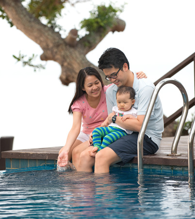 family outing: Happy Asian Family Playing in the pool Stock Photo