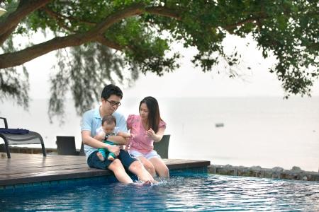 family picnic: Familia asiática feliz jugando en la piscina