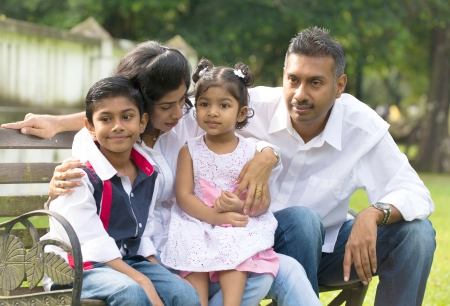 indian family sitting on the bench in the park photo