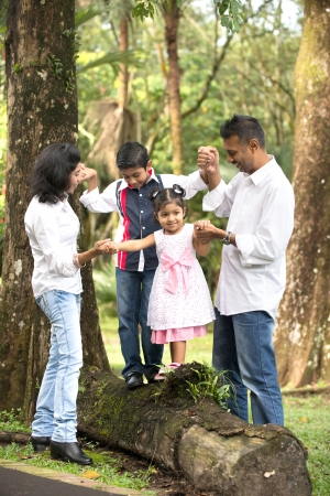asian trees: indian family teaching children to climb Stock Photo