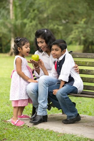 south asian: indian family outdoor eating healthy photo   Stock Photo