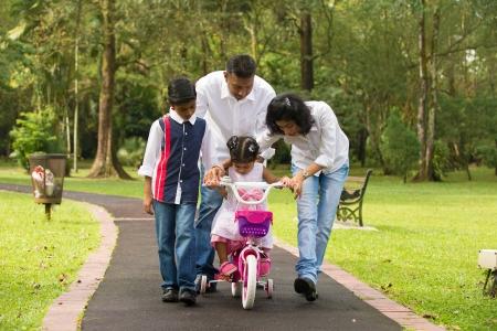 disfrutar: familia india guiar peque�a hija al ciclo Foto de archivo