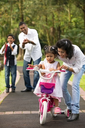 asian trees: indian family guiding little daughter to cycle