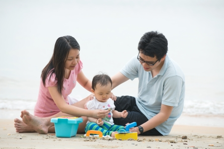 asian family playing on the beach photo