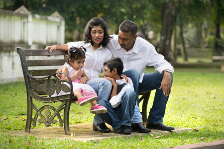 south asian: indian family sitting on the bench in the park