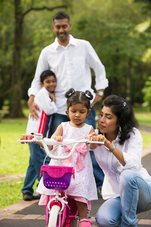 indian family guiding little daughter to cycle   photo
