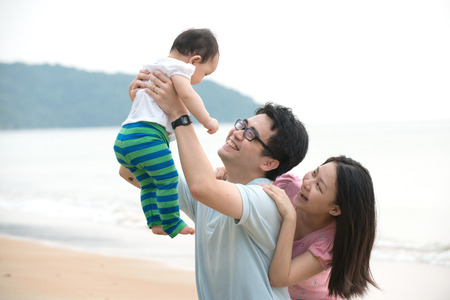family outing: chinese asian family playing on the beach   Stock Photo