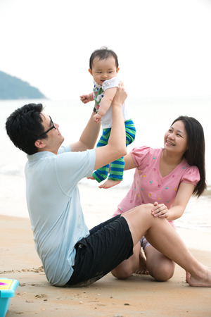 chinese asian family playing on the beach   photo