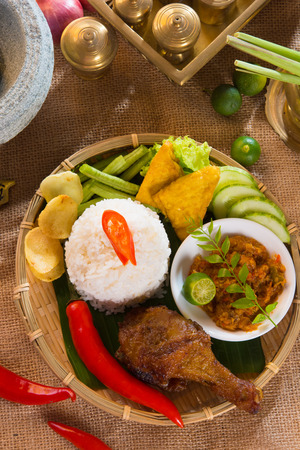 nasi: indonesian fried chicken rice on traditional background   Stock Photo