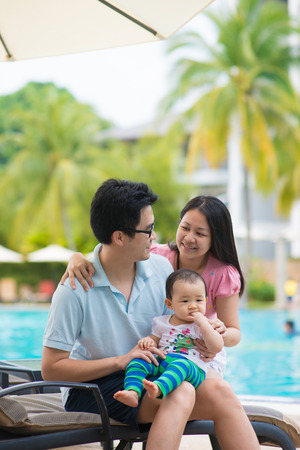 family outing: asian father , mother and daughter having holiday on a pool