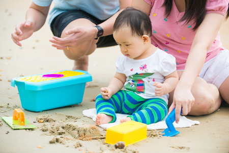 asian baby playing sand on the beach with father and mother photo