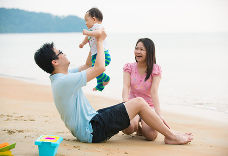 asian family enjoying quality time on the beach with father, mother and daughter Stock Photo
