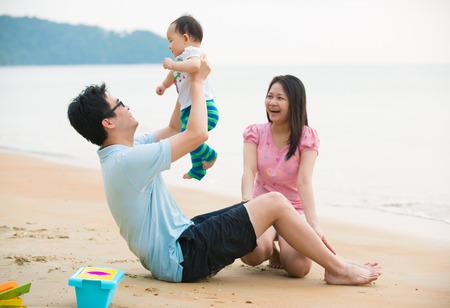 jugando: Familia asi�tica que disfruta de tiempo de calidad en la playa con el padre, la madre y la hija