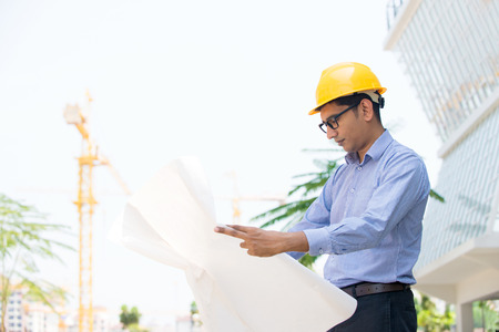 indian architect reading plans on construction site photo