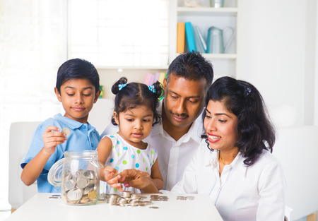 family planning: indian family teaching children on savings and financial planning