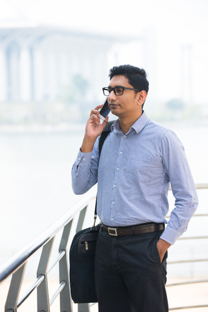 indian asian business male with cell phone and lake  photo