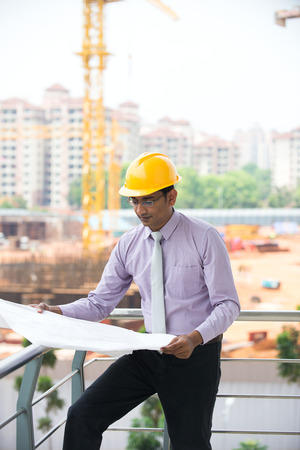 indian male architect reading plans with construction  photo