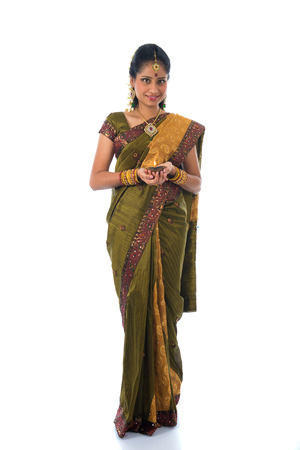 indian style sitting: indian female in traditional clothes with lamp full body Stock Photo