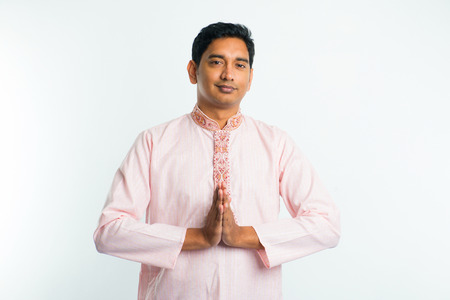 young indian male with  Pranamasana greetings sign on traditional dress with plain  Stock Photo
