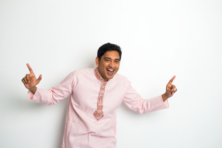 young indian male in traditional cloths celebrating bhangra photo