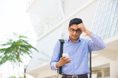 confused looking indian business male on a smartphone with office  Stock Photo