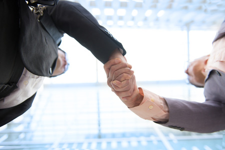 Close up image of hand shake against skyscrapers, low angle