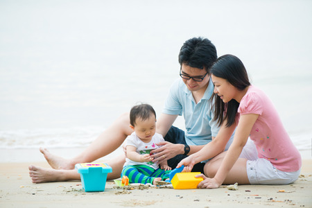 mom and dad: asian family enjoying quality time on the beach with father, mother and daughter