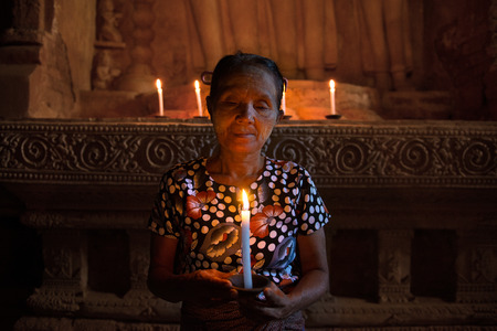 old asian woman praying in ancient temple with candle light photo