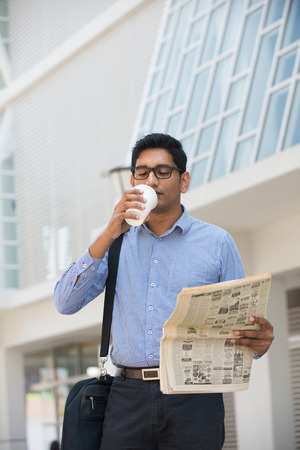 indian business man with coffee and papers outside his office   photo
