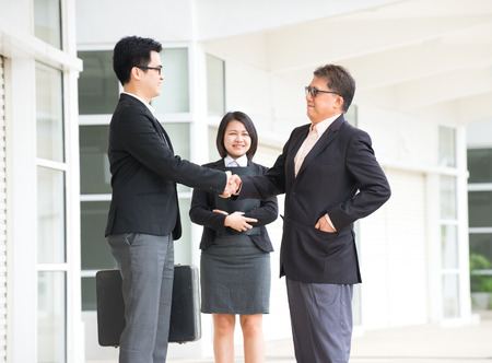 asian business handshake between senior and young business male   photo