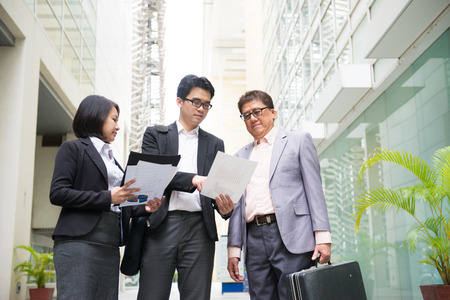 asian business team reporting to senior ceo with office background photo