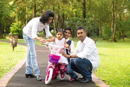 teaching adult: indian family teaching their kids cycling in the outdoor park
