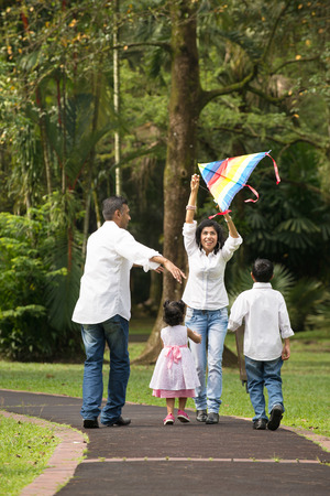 papalote: familia india jugando cometa en el parque al aire libre